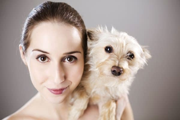 woman holding a small dog waiting for salt therapy